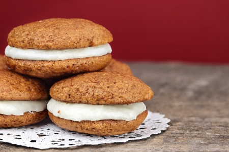 Stack of homemade Pumpkin Whoopie Pies or Moon Pies made with cream cheese frosting   photo