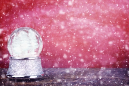 Empty Silver snowglobe against a red background with room for copy space   Stock Photo