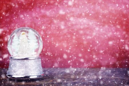 Silver snowglobe against a red background with room for copy space   photo