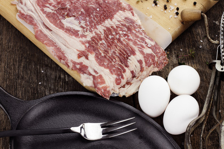 Breakfast ingredients, cast iron skillet and uncooked beef bacon with fresh eggs and herbs.