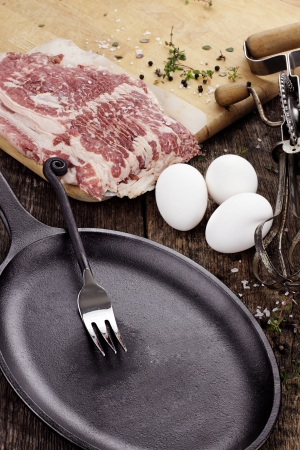 uncooked bacon: Cast iron skillet with uncooked beef bacon with fresh eggs.