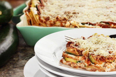 A serving of zucchini lasagna with fresh zucchini and casserole dish in background.