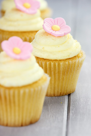 sugarcraft: Pretty yellow and pink cupcakes with extreme shallow depth of field and selective focus on center cupcake. Stock Photo