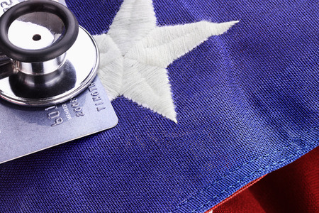 political and social issues: Stethoscope placed over American flag and credit card.