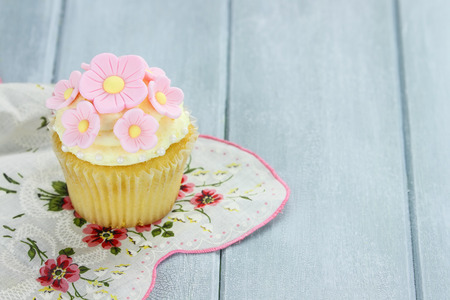 gumpaste: Pretty yellow and pink cupcake with extreme shallow depth of field and copy space. Stock Photo
