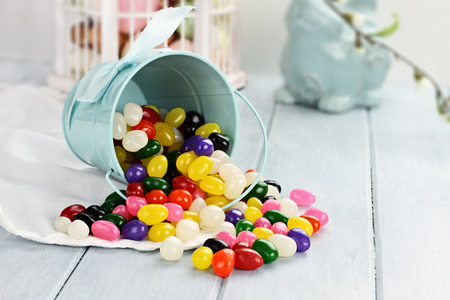 A blue tin bucket tipped over, spilling jelly beans onto a table  Shallow depth of field  photo
