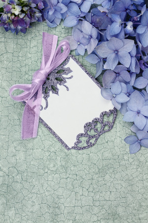Blank card and flowers over green craquelure  with room for your text. Stock Photo