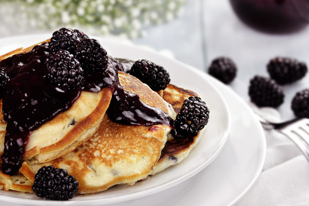 Delicious golden pancakes with fresh blackberries and jam. Extreme shallow depth of field. photo