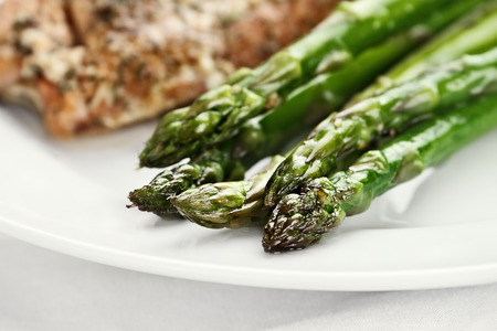 Freshly sauteed asparagus with salmon in background  Extreme shallow depth of field with selective focus on tip of asparagus  photo