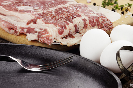 uncooked bacon: Uncooked beef bacon with fresh eggs and herbs