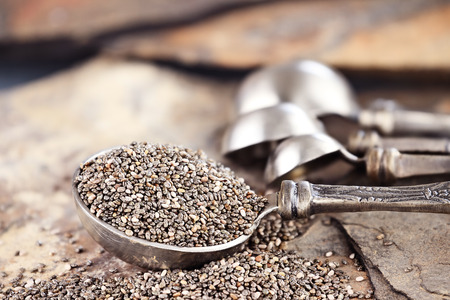 Tablespoon of healthy chia seeds with selective focus and extreme shallow depth of field  Imagens