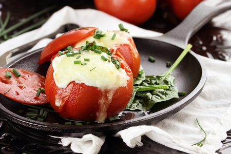 Eggs with mozzarella cheese baked in fresh tomatoes and garnished with chives. Extreme shallow depth of field. photo