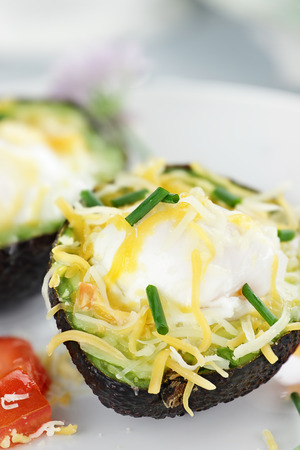 avacado: Eggs with cheddar cheese baked in fresh avocados and garnished with chives. Extreme shallow depth of field.