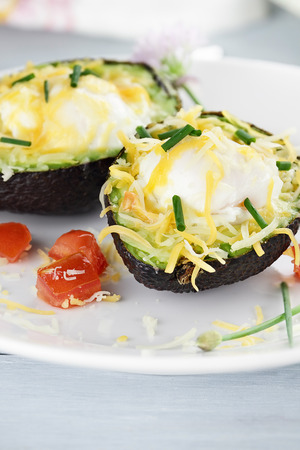 Eggs with cheddar cheese baked in fresh avocados and garnished with chives. Extreme shallow depth of field. photo