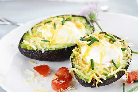 Eggs with cheddar cheese baked in fresh avocados and garnished with chives. Extreme shallow depth of field.