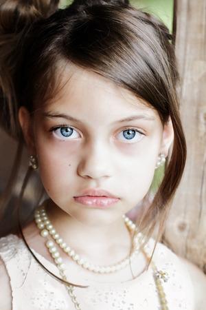 Jeune fille regardant directement dans la caméra, portant collier de perles vintage et cheveux tirés en arrière. Extreme profondeur de champ avec un accent sélectif sur les yeux. Banque d'images
