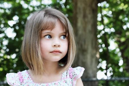 꼬리를 자른 머리를 가진 귀여운 소녀는 카메라에서 멀리 찾고 잘라. 필드의 극단적 인 얕은 깊이.