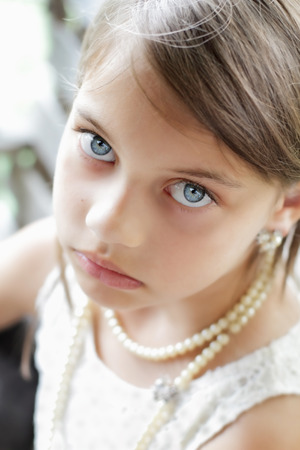 Young girl looking directly into the camera, wearing vintage pearl necklace and hair pulled back. Extreme shallow depth of field with selective focus on eyes. photo