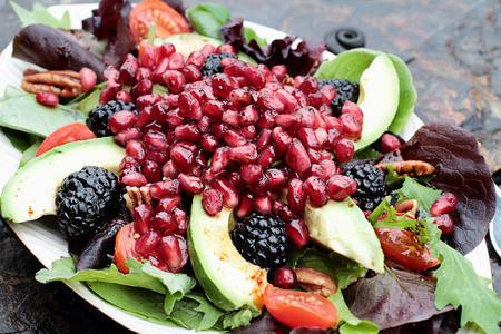 Une bonne salade à la grenade, l'avocat, les tomates, les amandes et la laitue argula sur un fond rustique. Banque d'images