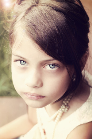 Young girl looking directly into the camera, wearing vintage pearl necklace and hair pulled back. Extreme shallow depth of field with selective focus on eyes.