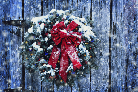 Rustic Christmas wreath on old weathered door with Christmas lights in a snow storm. 스톡 콘텐츠