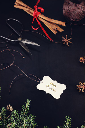"""antique scissors: Tag di Natale con la citazione """"Merry Christmas"""" con la canapa pungiglione, cannella, anice e forbici antiche su sfondo scuro."""