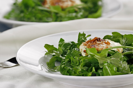 goat cheese: Fried Goat Cheese And Arugula Salad served with a white wine vinaigrette. Extreme shallow depth of field with selective on salad in foreground. #FoodLove2014