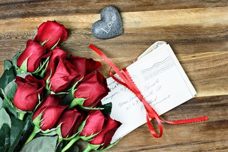 long stem roses: Long stem red roses with a stack of old letters tied with a red ribbon and card a little stone heart with the word love. Stock Photo