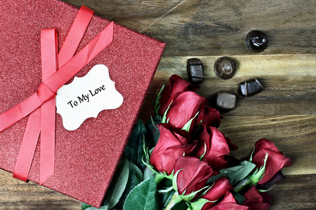 long stem roses: Gift box with long stem red roses and chocolates over an old wooden background with room for copy space.