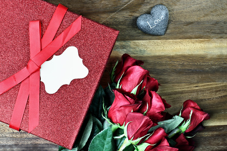 long stem roses: Gift box with long stem red roses and blank card over an old wooden background with room for copy space.