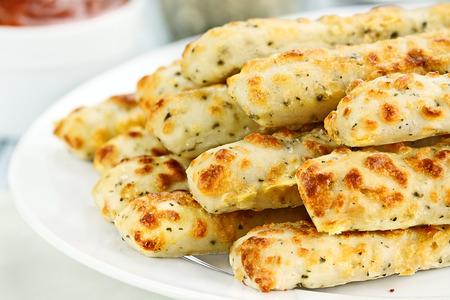 gressins: Frais d'or, des b�tons de fromage � la sauce marinara et parmesan en arri�re-plan. Faible profondeur de champ.