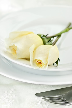 long stem roses: Romantic table setting with long stem yellow roses. Extreme shallow depth of field with selective focus on rose in foreground. Stock Photo