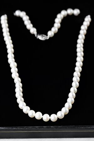 Beautiful pearl necklace in a black case. Extreme shallow depth of field with selective focus on foreground.
