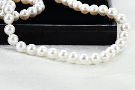 String of a beautiful pearl necklace lying over a black case. Extreme shallow depth of field.