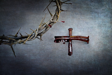 Crown of thorns and cross of naiils with blood puddled on ends. Stock Photo