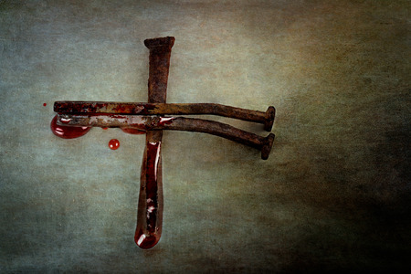Cross of naiils with blood puddled on ends and sprinkling around edges with room for text. Stock Photo