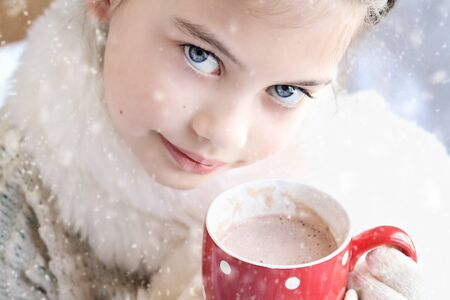 warmly: Young girl dressed warmly, drinking hot chocolate outdoor in the winter. Selective focus on childs eyes with extreme shallow depth of field.