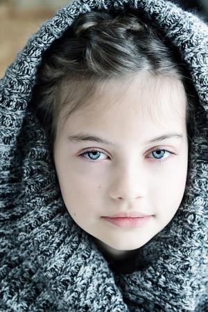 Tiro del estudio de una hermosa joven en un suéter con capucha con poca profundidad de campo. Foto de archivo