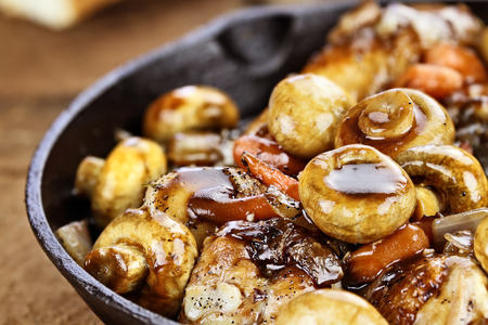 Detailed shot of Coq Au Vin in rustic cast iron pan with shallow depth of field. photo