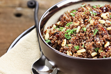 Bowl of Quinoa Pilaf with parsley, pine nuts and cranberries.