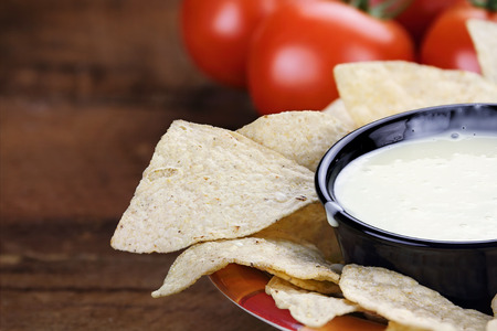 blanco: Queso Blanco or White Cheese Sauce with corn tortilla chips and fresh tomatoes. Extreme shallow depth of field with selective focus on cheese dip.