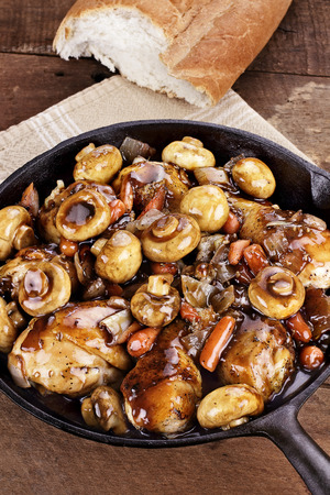Coq Au Vin in rustic cast iron pan with shallow depth of field.