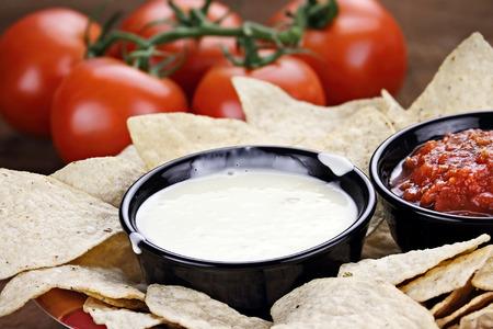 Frischkäse oder Weißkäse-Sauce mit Mais Tortilla-Chips, Salsa und frischen Tomaten. Geringe Schärfentiefe mit selektiven Fokus auf Käse-Dip. Standard-Bild - 39027664
