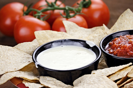 blanco: Queso Blanco or White Cheese Sauce with corn tortilla chips, salsa and fresh tomatoes. Shallow depth of field with selective focus on cheese dip. Stock Photo