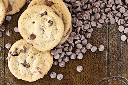 chocolate chips cookies: Chocolate chips cookies with loosely scattered chocolate chips over a rustic background. Perfect for the May 15th National Chocolate Chip Day! Stock Photo