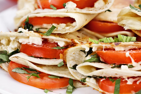 goat cheese: Vegetarian wraps made with goat cheese or feta, tomatoes, mozzarella and fresh herbs, Extreme shallow depth of field.