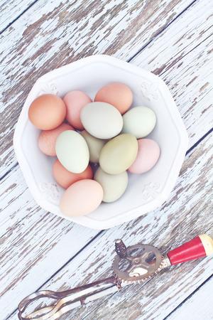 farm fresh: Colorful fattoria uova fresche di gallina provenienti da galline ruspanti con un frullino per le uova antico su un fondo rustico in legno. Archivio Fotografico