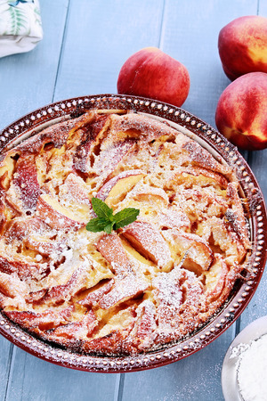 powered: Freshly baked Peach Clafouti with powered sugar. Extreme shallow depth of field with selective center of dish.