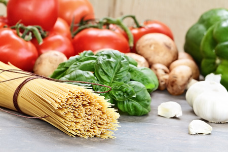 italian cuisine: Italian cuisine ingredients of spaghetti, basil leaves, garlic, mushrooms, peppers and fresh tomatoes with extreme shallow depth of field.