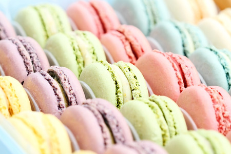 Box of fresh colorful macarons. Extreme shallow depth of field with selective focus on center green macaron. Stockfoto